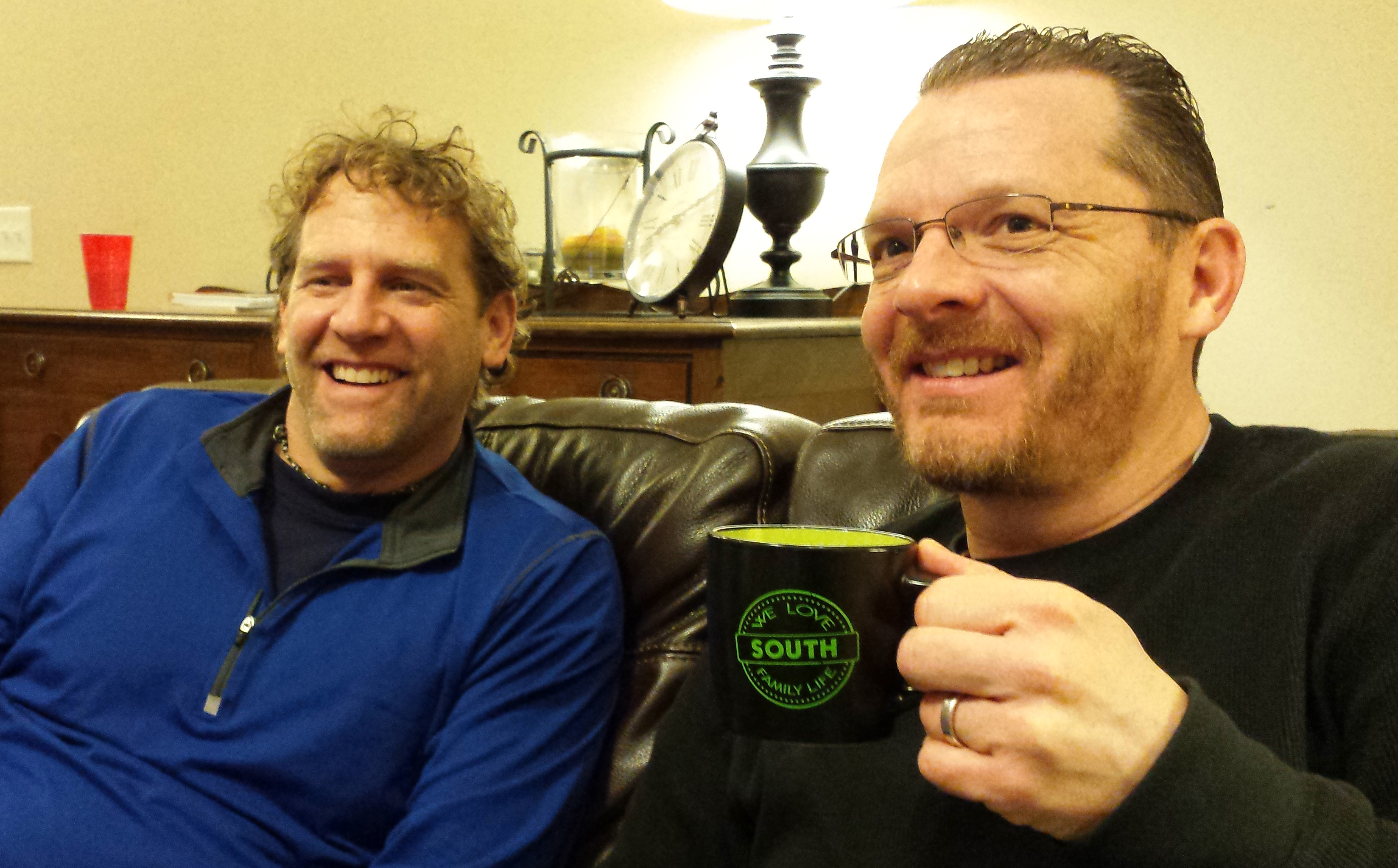 Two guys laughing and drinking coffee together on a leather couch.