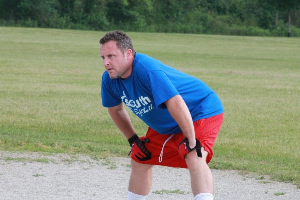 A men's softball player running the bases at an exciting church softball game.