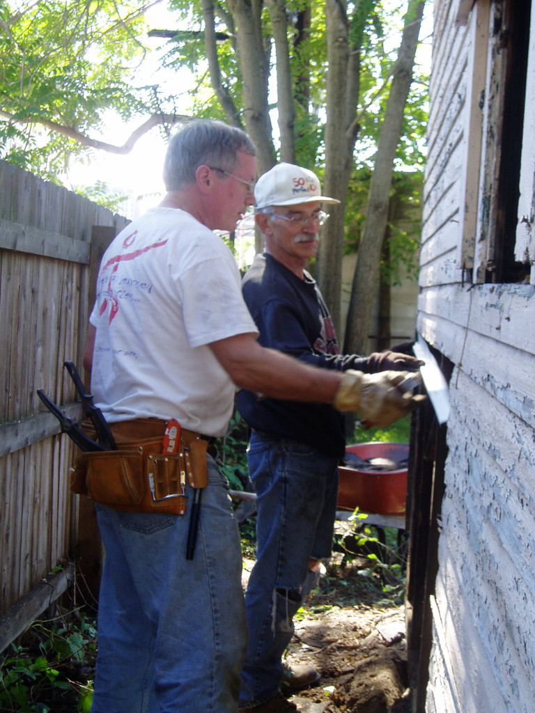 Two men from different generations, problem solving a siding issue on a men's work project.