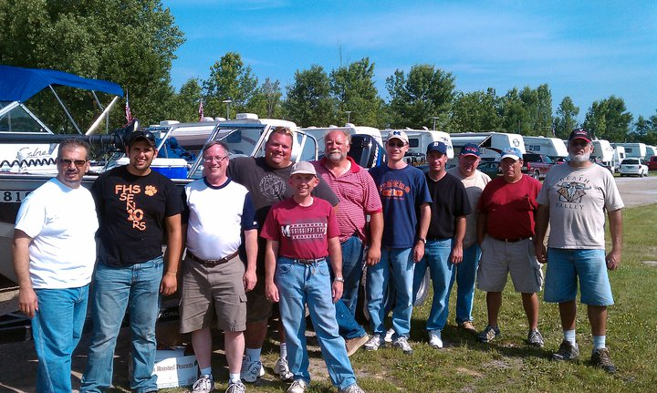 A group of men standing next to a boat on their Walleye Fishing Trip