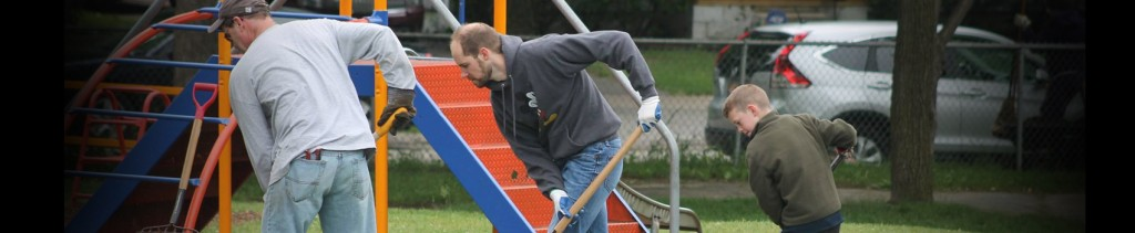 The youth pastor, a dad, and an 7-year old working together to rake the playground at Sarginson Park in Flint