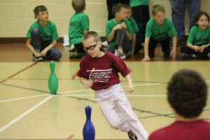 An upper elmentary-age is running his fastest in a race at the Awana games