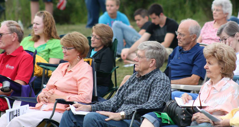 Happy people, from different generations, enjoying an outdoor worship service